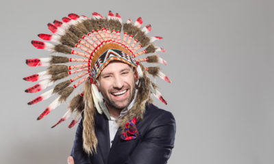 Portrait of happy businessman wearing indian headdress, laughing at the camera. Studio shot, one person, grey background. Humor i ledelse